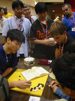 Three Japanese professional Go players observe some younger amateurs as they dissect a life and death problem in the corner of the board, at the US Go Congress in Houston, 2003.