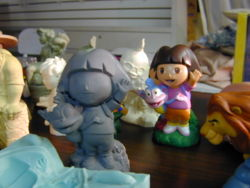 Dora the Explorer sculpture, and the finished painted toy based on it.
