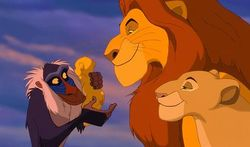 Rafiki holds Mufasa and Sarabi's newborn lion cub, Simba.