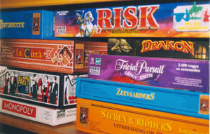 A shelf full of board games, including Risk, Monopoly and Trivial Pursuit.