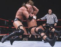 Steve Austin hits the Stone Cold Stunner on Triple H.